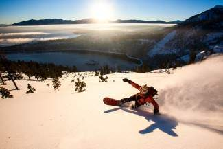 A backcountry snowboarder shreds above Emerald Bay.