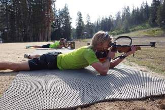 Local athletes Jordan McElroy and Patrick Johnson shoot from the prone position in a past summer biathlon at the Auburn Ski Club Training Center, which will host the US Biathlon summer national championships this Friday through Sunday.