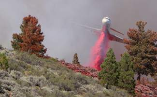 An air tanker drops retardant on the Boca Fire while flying through thick smoke Monday afternoon.