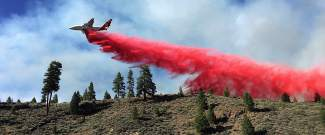 In all, four air tankers (including this one from CAL FIRE) were called to the scene Monday afternoon to battle the fire burning east of the dam at Boca Reservoir.