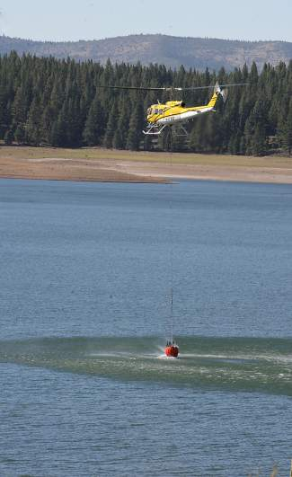 A helicopter dips into Boca Reservoir Monday afternoon to help battle the Boca Fire.