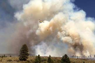 A helicopter dumps a load of water on Boca Fire Monday afternoon. The fire, the cause of which remains under investigation, charrred 84 acres before several regional crews put it out at about 10 p.m.
