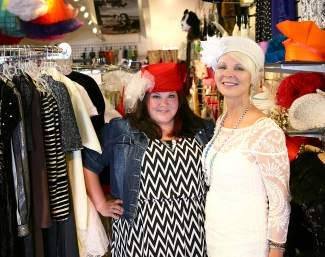 Sara Turner, left, and Annette Summers model some of Dress The Party's hat wear Wednesday afternoon at the shop. The duo plan to maintain much of what the store offers — while moving forward with some exciting changes.