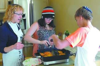 Rabbi Beth Beyer makes latkes with religious school students Eliana Sass and Sawyer Thompson in preparation for Hanukkah.
