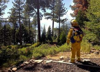 Brush fires can start faster than you might think; here, a firefighter surveys the scene during the summer of 2013 after a spot fire started off Rainbow Avenue in Kings Beach.