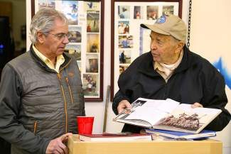 Local EAA chapter President Tim LoDolce and George Grupe browse through military history.