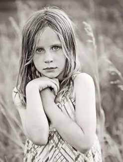 Serious Little Girl In Field