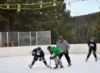 Hans Baumann, volunteer program coordinator, drops the puck during a Truckee-Donner Recreation & Park District youth hockey league game recently. The new league has about 50 participants.