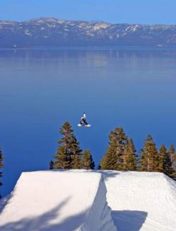 A snowboarder launches off a jump at Homewood Mountain Resort, with Diamond Peak Resort visible in the distance.