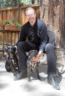 Craig Gummer and his dogs, Buck and Missy, sit on the patio at Fondue Blue. Craig planted the surrounding flowers in honor of his wife Marcia, who died one year ago.