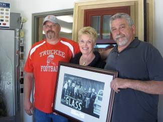 Jake, Sue, and Ben Moule hold a photo of Ben's father's glass shop in Grass Valley, which Ben and his eight brothers helped operate.