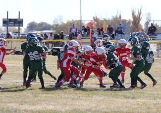 Led by Jason Roth, the Truckee Mitey-Mite Red defense swarms a Fallon runner during their 32-0 win on Saturday.