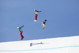 American Faye Gulini, right, soars over a jump during the women's Olympic snowboardcross on Tuesday. Gulini placed fourth.