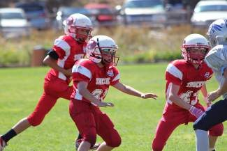 Owen Slusher and Connor McMullen seal the edge for Jack Watters as he runs the ball Saturday.
