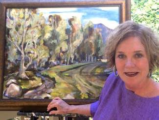 June Forman stands by one of her paintings, this one showing Busterback Ranch in Idaho's Stanley Basin.