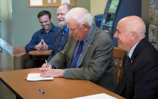 From left: Taylor Tiraterra, Sierra College, Tahoe-Truckee history professor (background), Chico State Vice President for Student Affairs Drew Callandrella, Chico State President Paul Zingg and Sierra College President William Duncan sign the dotted line sealing a formal transfer agreement between Sierra College and Chico State.