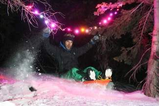 Zachary Holmes takes to the air during a well-lit night sledding session last winter.
