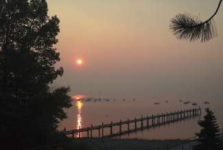 The sun rises through a smoky sky in Tahoe City on Friday. The poor air quality caused by Sierra wildfires has forced the cancellation of numerous sporting events.