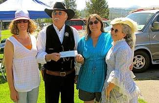 Chelsea Walterscheid, left, advisor to the TDHS Board and Chaun Mortier,  TDHS president, third from left, receive a $500 donation from Cap't Culpepper and Irish Rose of the Railroad Regulators.