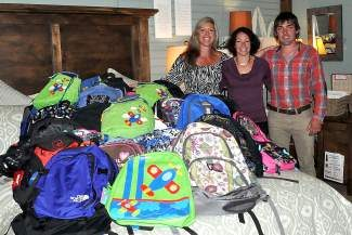From left: Julie Huck, Brooke Bentley and Spencer Wood, White Buffalo employee and son of Jerry and Donna Wood, show off the back packs to be distributed in Truckee.