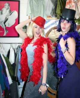 """THS seniors Hailey Perkins and Emily Houghton choose outfits from Unique Boutique. Given the theme for this year's fashion show, """"An Evening with the Stars,"""" the girls went glam for a bit of retro fun and sparkle."""