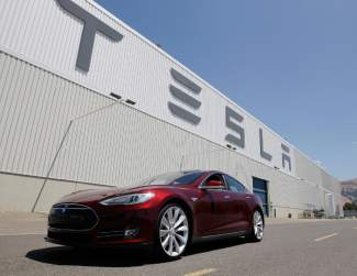 This June 22, 2012, file photo shows a Tesla Model S driving outside the Tesla factory in Fremont, Calif.