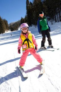 Signing up your young child for a ski or snowboard lesson can help him or her learn the ropes on the slopes.