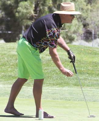 Without shoes, former NFL quarterback Jim McMahon lines up a putt on the 16th green.