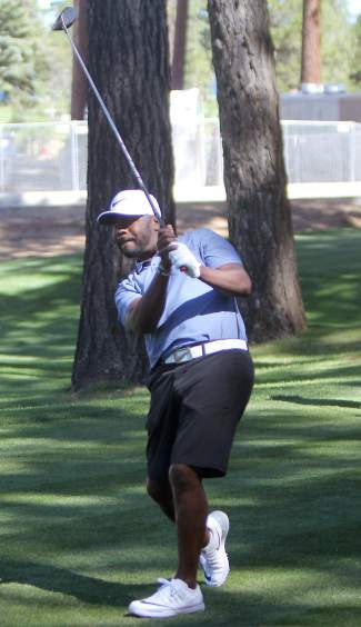 NFL Hall of Famer Marshall Faulk uses body language to steer his tee shot on the eighth hole Tuesday.