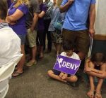 """A child looks down at his Keep Squaw True """"DENY"""" sign at Thursday's meeting in Kings Beach."""