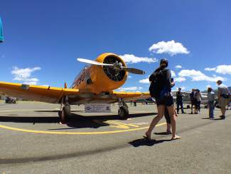 A woman walking by stops to admire the Commemorative Air Force's AT6 SNJ airplane.