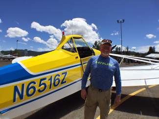 Doug Robbins poses in front his fully restored 1962 Piper Pawnee 225.