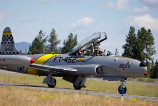 "Gregory ""Wired"" Colyer waves from a Lockheed T-33 to the people lining a  Truckee Tahoe Airport runway Saturday."