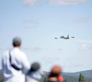 "People watch as Gregory ""Wired"" Colyer soars in the air in a  Lockheed T-33 at Truckee Tahoe Airport on Saturday."