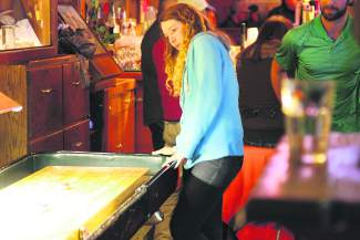 Jessica James watches as her teammate's shuffleboard disc slides down the board during the Bar Olympics on Tuesday.