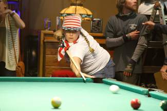 Jenefer Gallagher strikes a shot to the corner pocket during the pool competition of the Bar Olympics on Tuesday.
