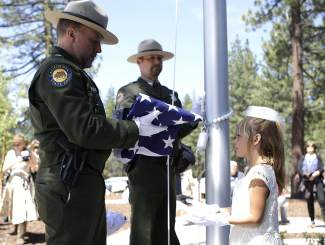 From left, California State Parks superintendents Matt Green and Scott Elliot conduct a flag raising with Abigail Quadros and Cora Medhurst (not pictured), descendants of Pioneer Memorial bronze caster Louis De Rome.