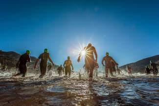Athletes wade into the water off of West End Beach at the start of the Donner Lake Triathlon.