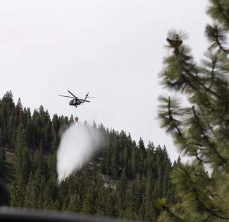 A helicopter flies overhead Saturday at Diamond Peak Ski Resort, releasing water on a fake spot fire.