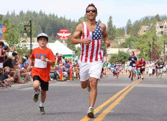Father and son Paul and Ethan Raymore near the finish line of the Firecracker Mile. The pair finished together in 6:20.