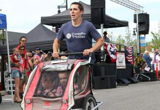 Pushing two infants in a stroller, Alexander Savitsky races to the win in the fun wave of the Firecracker Mile.