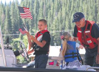 Flag-waving kids ride along with the U.S. Coast Guard float.