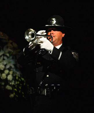An officer plays taps in honor of slain Carson City Deputy Carl Howell Thursday in Reno.