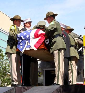 Deputy Carl Howell's casket is unloaded from the back of a Carson City Fire Department engine at his funeral in Reno Thursday.