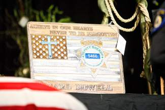 A plaque honoring Carson City Deputy Carl Howell is seen onstage Thursday at his funeral ceremony in Reno.