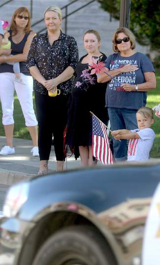 A young boy waves an American flag as the procession passes to the services of Carson City Sheriff's Deputy Carl Howell Thursday morning.
