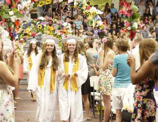 From left, Incline High School seniors Caitlin and Kimberly May enter the school's gym for the June 18 commencement ceremony while a large crowd watches on.