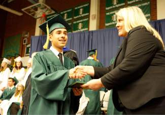 Incline High School graduate Allen Magdaleno accepts his diploma from board trustee Lisa Ruggerio.