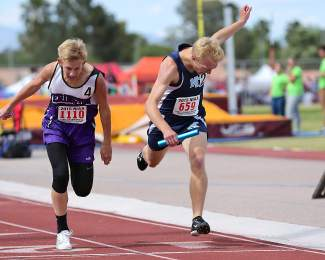 North Tahoe senior James Palacio edges Yerington's Kevin Kirk in a photo finish for first place in the 4 x 800 relay in the Division III state championships. Both runners fell after crossing the finish line.
