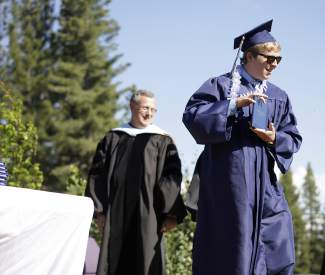 North Tahoe grad Miles Johansen shows off his diploma to his fellow classmates, family and friends during Thursday's graduation, while Tahoe Truckee Unified School District Superintendent Rob Leri watches on.